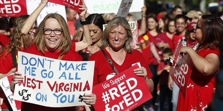 Arizona teachers and education advocates march at the Arizona Capitol protesting low teacher pay and school funding Wednesday, March 28, 2018, in Phoenix. (AP Photo/Ross D. Franklin)