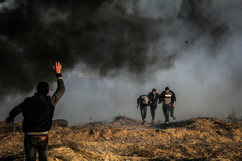 Palestinians protesters run for cover from Israeli tear gas during clashes with Israeli troops along the border between Israel and Gaza Strip, in the eastern Gaza Strip, 01 April 2018. According to reports, nine Palestinians were injured during the clashes along the border with Israel. Protesters plan to call for the right of Palestinian refugees across the Middle East to return to homes they fled in the war surrounding the 1948 creation of Israel. (Photo by Momen Faiz/NurPhoto/Sipa USA)(Sipa via AP Images)