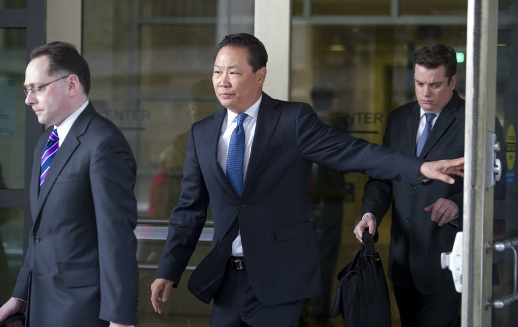Stephen Kim, a former State Department expert on North Korea, center, leaves federal court in Washington, Wednesday, April 2, 2014, after a federal judge sentenced him to 13 months in prison for passing classified information to a journalist.  (AP Photo/Cliff Owen)