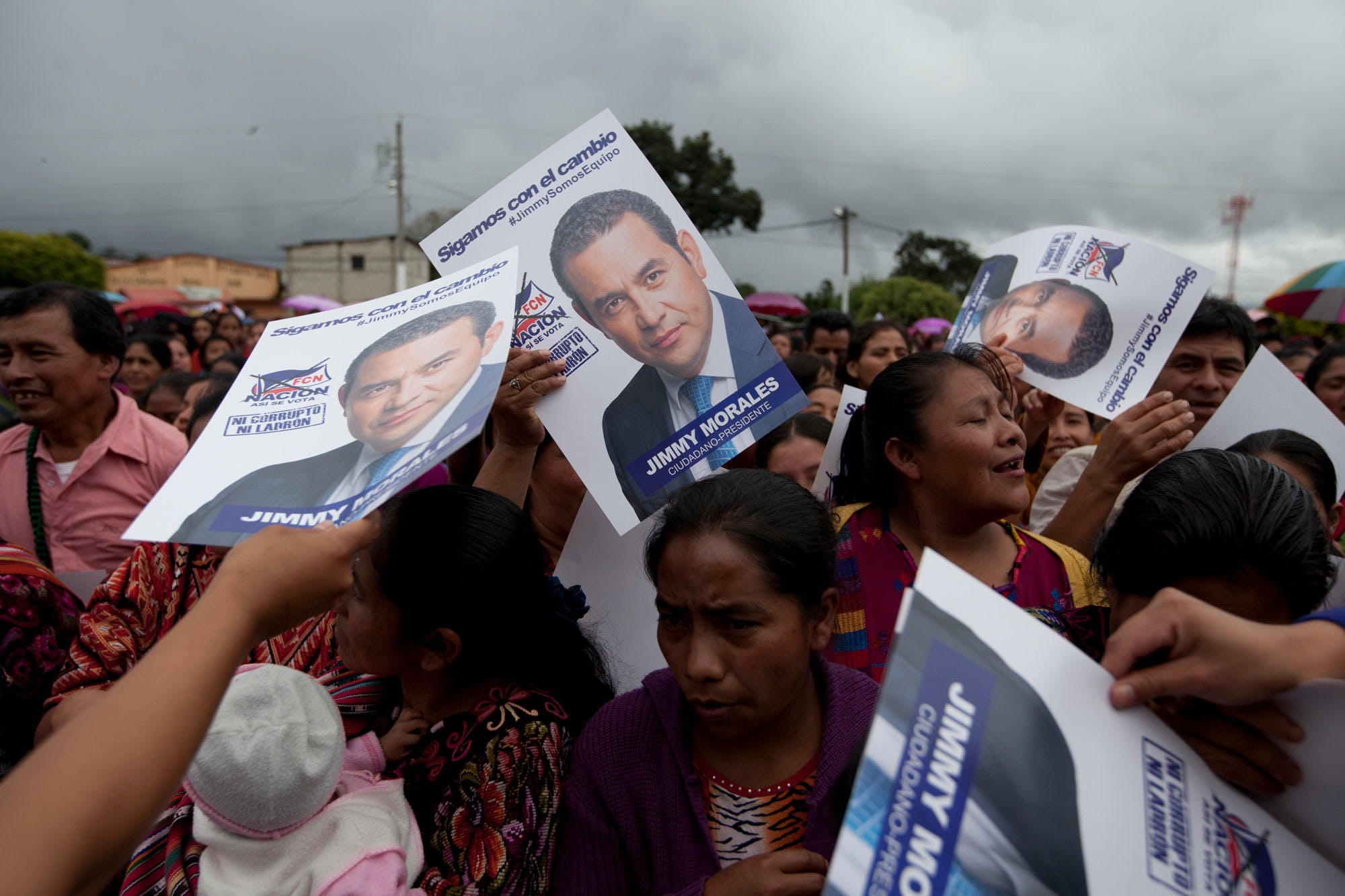 Campaign posters featuring presidential candidate Jimmy Morales of the National Front of Convergence party, are passed out during a rally, in Chichicastenango, Guatemala, Saturday, Oct. 17, 2015. Voters will head to the polls on Oct. 25 to choose a new leader in the presidential run-off. (AP Photo/Moises Castillo)