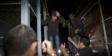FILE - In this Aug. 29, 2014 file photo, immigration officials remove Central American migrants from a northbound freight train during an after midnight raid by federal police in San Ramon, Mexico. Following a surge in child migrants reaching the U.S. border in 2014, Mexican authorities said Tuesday, March 3, 2015 that they staged more than 150 raids over the last year on the train known as