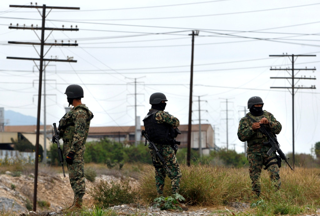 Three members of the Mexican Army watch at the residencial Anahuac neighbordhood in Monterrey, Nuevo Leon State, Mexico on February 5, 2012, after clashes between a gruop of gunmen and Mexican Army. More than 40.000 people have been killed in rising drug-related violence in Mexico since December 2006, when President Felipe Calderon deployed soldiers and federal police to take on organized crime. AFP PHOTO/Julio Cesar Aguilar (Photo credit should read Julio Cesar Aguilar/AFP/Getty Images)