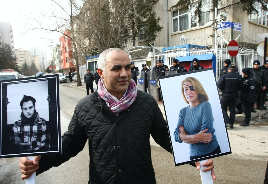A Turkish journalist in Ankara, on February 24, holds pictures of two journalists, French photojournalist Remi Ochlik (L) and Sunday Times correspondent Marie Colvin, killed in an alleged rocket attack by Syrian regime forces against a makeshift opposition media center in the besieged city of Homs in Syria on February 22, during a demonstration by journalists denouncing violence against members of the media and the brutality of Syrian President Bashar al-Assad's regime.  AFP PHOTO / ADEM ALTAN (Photo credit should read ADEM ALTAN/AFP/Getty Images)