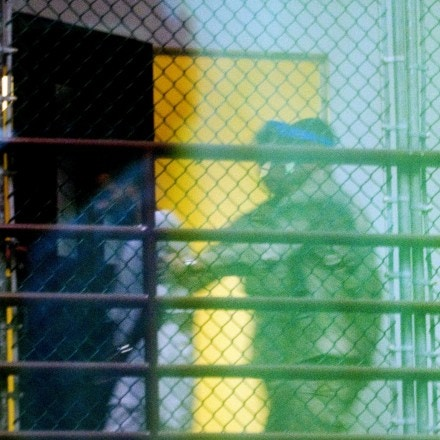 This image reviewed by the US military shot through a one way mirror shows guards moving a detainee from his cell in Cell Block A of the