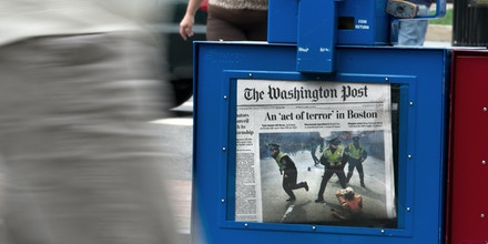 Pedestrians pass next to a newspaper vending machine offering The Washington Post featuring the aftermath of the Boston bombings on its front page in Washington DC, April 16, 2013. US President Barack Obama branded the Boston bombings a