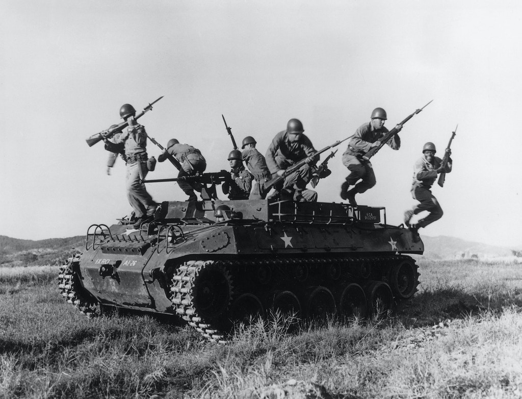 17th March 1954:  American soldiers leaping from an armoured personnel carrier during exercises in Korea.  (Photo by Three Lions/Getty Images)