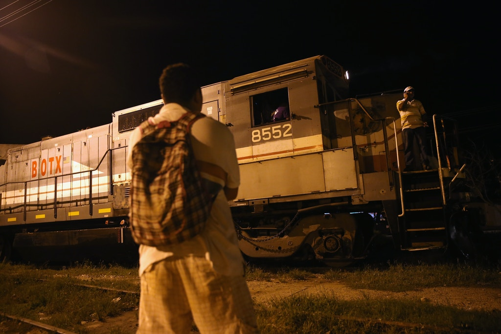 "TENOSIQUE, MEXICO - SEPTEMBER 15:  A Central American watches as a freight train arrives on September 15, 2014 in Tenosique, Mexico. Many migrants have perished riding atop ""La Bestia"" or The Beast freight train on their journey to the U.S. border.  (Photo by John Moore/Getty Images)"