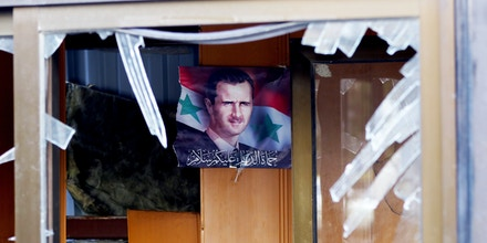 A picture taken on February 9, 2016 shows, through a broken window, a portrait of Syrian President Bashar Assad hanging on a wall in a building next to the site of a suicide attack at a police officer's club in the Masaken Barzeh district of the capital Damascus. The Syrian Observatory for Human Rights said about 20 people had also been wounded, adding that policemen were among the dead and injured. / AFP / LOUAI BESHARA (Photo credit should read LOUAI BESHARA/AFP/Getty Images)