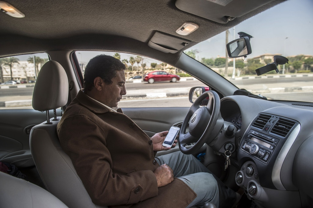 Ahmed Mahmoud, 53, an Egyptian driver working for Uber Transportation Company in Egypt waits for customers on February 23, 2016 in Cairo.<br /><br /><br /> The use of the smartphone applications has taken off in Cairo, so much so that Uber says the Egyptian capital is one of its fastest growing markets. But not everyone is happy. Taxi drivers have been protesting against them for weeks as they lose more and more clients to the rival services. / AFP / KHALED DESOUKI / TO GO WITH AFP STORY BY TONY GAMAL        (Photo credit should read KHALED DESOUKI/AFP/Getty Images)