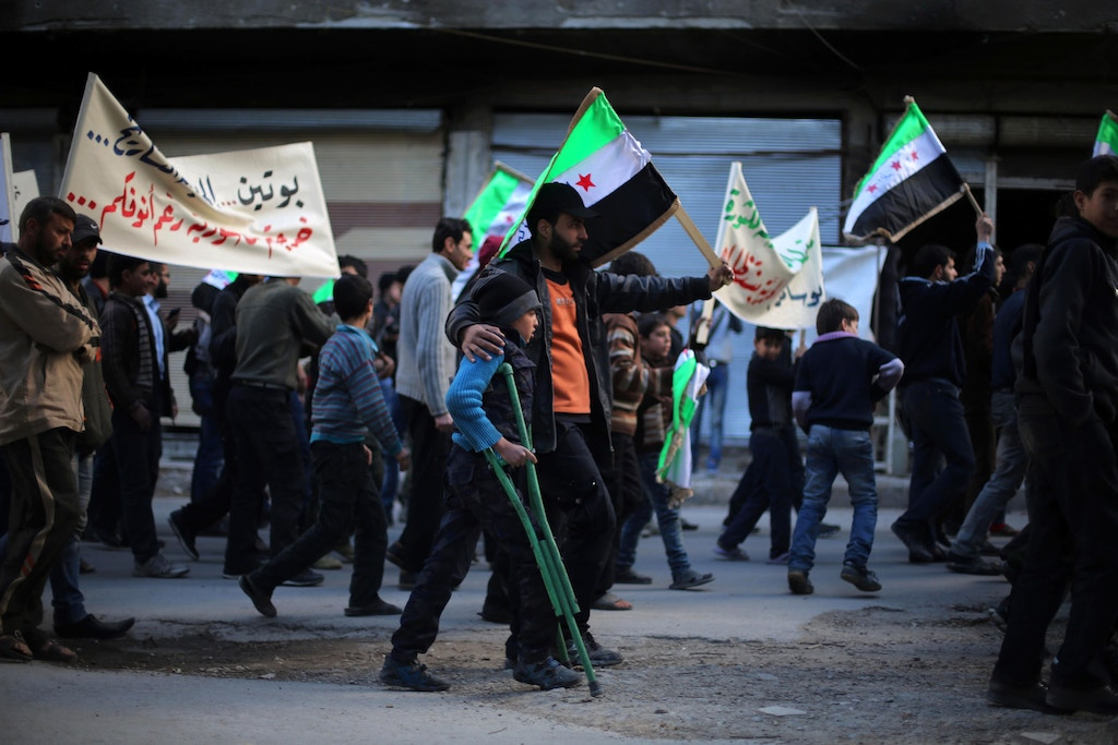 Protesters hold flags and placards during an anti-regime demonstration in the rebel-held town of Saqba, on the outskirts of the Syrian capital Damascus, on March 16, 2016.<br /><br /><br /><br /><br /><br /><br /><br /> Syria's war is entering its sixth year with a glimmer of hope that a landmark ceasefire and a push for peace could help resolve a conflict that has sent hundreds of thousands fleeing to Europe. / AFP / AMER ALMOHIBANY        (Photo credit should read AMER ALMOHIBANY/AFP/Getty Images)