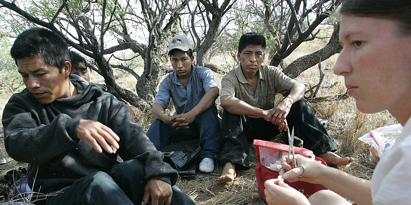 "Amber Stenson of ""No More Deaths,"" a group of volunteers who provide water, food and first aid to illegal migrants crossing through the southern Arizona desert from Mexico, treats the blistered feet of men who were camped in the brush near the town of Aravaca Thursday, July 21, 2005.  (Photo by Robert Gauthier/Los Angeles Times via Getty Images)"