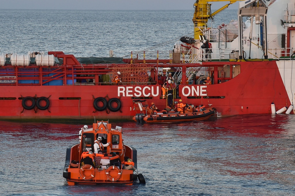 "Migrants and refugees are transferred from the Topaz Responder ship run by Maltese NGO ""Moas"" and the Italian Red Cross to the Vos Hestia ship run by NGO ""Save the Children"", on November 4, 2016, a day after a rescue operation off the Libyan coast in the Mediterranean Sea.<br /><br /><br /><br /><br /><br /> Around 750 migrants were rescued across the Mediterranean Thursday by the Italian coast guard, a Frontex ship, a Save The Children vessel, German NGO Jugend Rettet's Iuventa and two boats run by the Malta-based MOAS (Migrant Offshore Aid Station). But at least 110 migrants are feared drowned after they were forced at gunpoint to set sail from Libya, while many more may have died in a separate shipwreck, survivors said. / AFP PHOTO / ANDREAS SOLARO        (Photo credit should read ANDREAS SOLARO/AFP/Getty Images)"