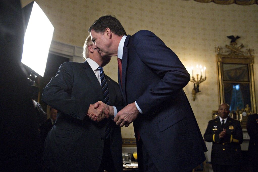 "WASHINGTON, DC - JANUARY 22: U.S. President Donald Trump (L) shakes hands with James Comey, director of the Federal Bureau of Investigation (FBI), during an Inaugural Law Enforcement Officers and First Responders Reception in the Blue Room of the White House on January 22, 2017 in Washington, DC. Trump today mocked protesters who gathered for large demonstrations across the U.S. and the world on Saturday to signal discontent with his leadership, but later offered a more conciliatory tone, saying he recognized such marches as a ""hallmark of our democracy."" (Photo by Andrew Harrer-Pool/Getty Images)"