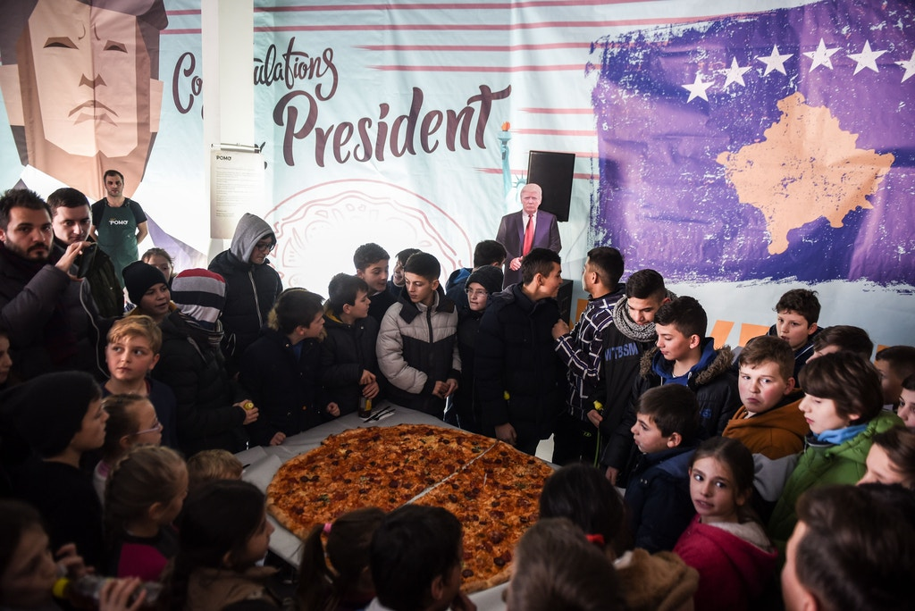 Children gather around a pizza at a restaurant near the town of Ferizaj on January 28, 2017, where  45 pizzas were given for free in honor to the new elected  President of the United States of America. / AFP / Armend NIMANI        (Photo credit should read ARMEND NIMANI/AFP/Getty Images)