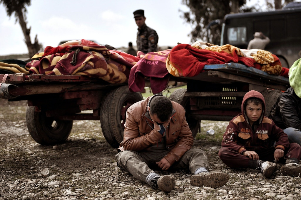 TOPSHOT - Relatives mourn as bodies of Iraqi residents of west Mosul killed in an airstrike targeting Islamic State (IS) group jihadists are placed and covered with blankets on carts on March 17, 2017. / AFP PHOTO / ARIS MESSINIS        (Photo credit should read ARIS MESSINIS/AFP/Getty Images)