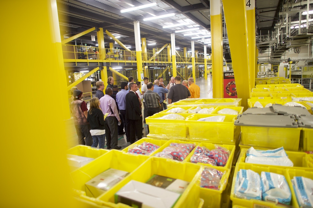 ROBBINSVILLE, NJ - AUGUST 2: Job seekers tour the Amazon Fulfillment Center during an Amazon jobs fair on August 2, 2017 in Robbinsville, New Jersey. The American commerce company is hosting 'Amazon Jobs Day' with job fairs across the country to hire 50,000 positions for their fulfillment centers nationwide. The more than 1 million square foot facility holds tens of millions of products and features more than 14 miles of conveyor belts, employing more than 4,000 workers who pick, pack, and ship orders. (Photo by Mark Makela/Getty Images)