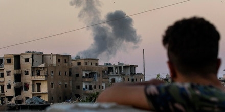 RAQQA, SYRIA - AUGUST 18:  Smoke rises from a building believed to be housing ISIS, after being hit by a mortar round fired from a United States military base on August 18, 2017 in western Raqqa.The MFS is a group of Assyrian Christians who fight alongside the Syrian Democratic Forces (SDF) in Raqqa. The SDF was created in 2015 with the specific purpose of fighting ISIL and was armed by former US President Obama. The second Battle of Raqqa was launched in June 2017 and is the fifth and final phase of the Raqqa Campaign by the SDF.  (Photo by Rick Findler/Getty Images)