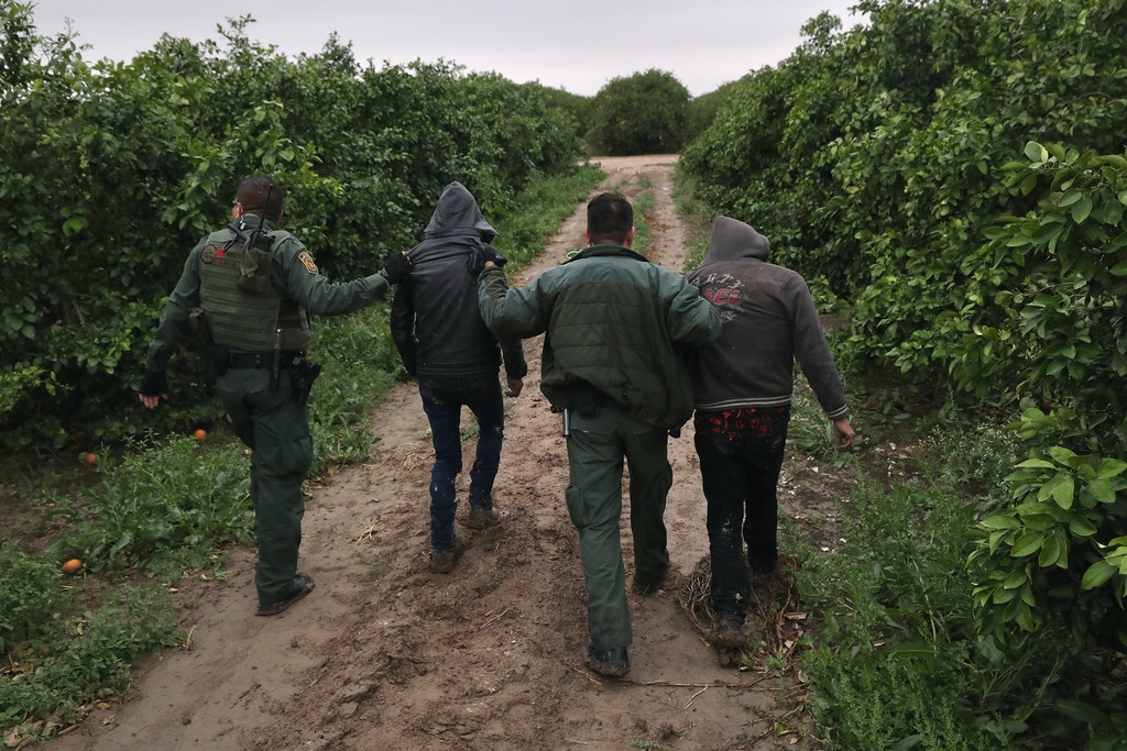 MCALLEN, TX - FEBRUARY 22:  U.S. Border Patrol agents detain  undocumented immigrants from Central America after capturing them in a grapefruit orchard on February 22, 2018 near McAllen, Texas. The group had crossed from Mexico into Texas only moments before.  (Photo by John Moore/Getty Images)