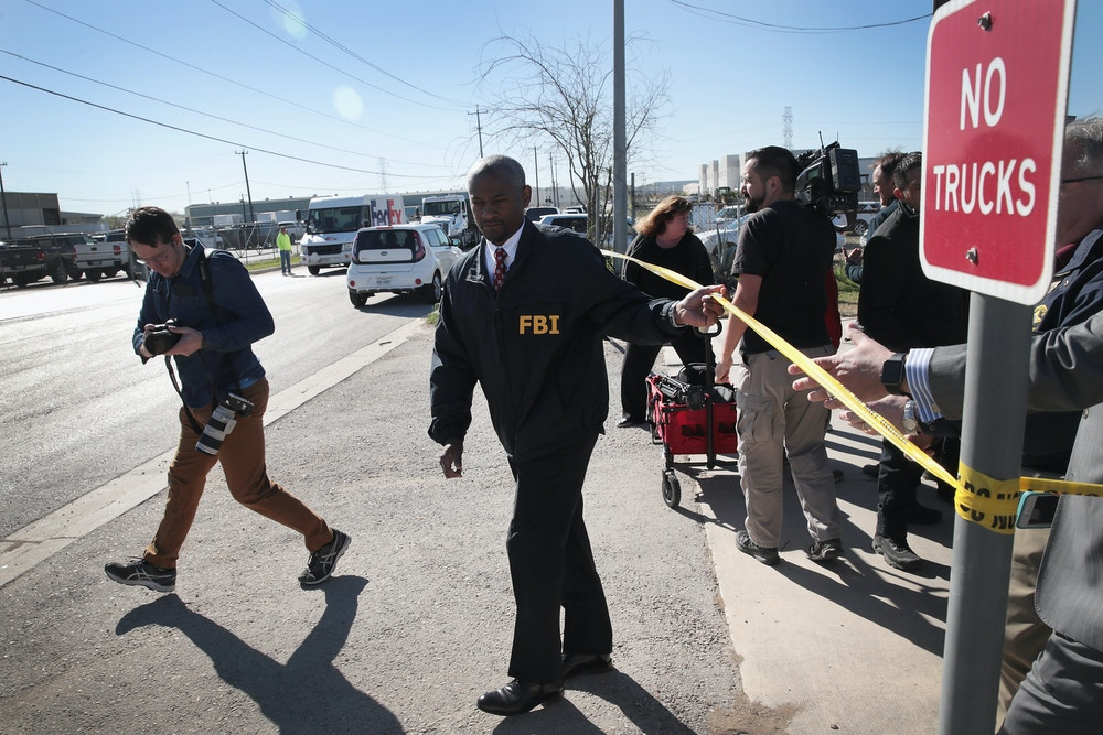 SCHERTZ, TX - MARCH 20:  FBI and ATF agents return to their investigation following a news briefing outside a FedEx facility following an explosion on March 20, 2018 in Schertz, Texas. A package exploded while being transported on a conveyor shortly after midnight this morning causing minor injuries to one person. The explosion is believed to be related to several recent package bombs that have been detonated in Austin, Texas, about an hour's drive from Schertz.  (Photo by Scott Olson/Getty Images)