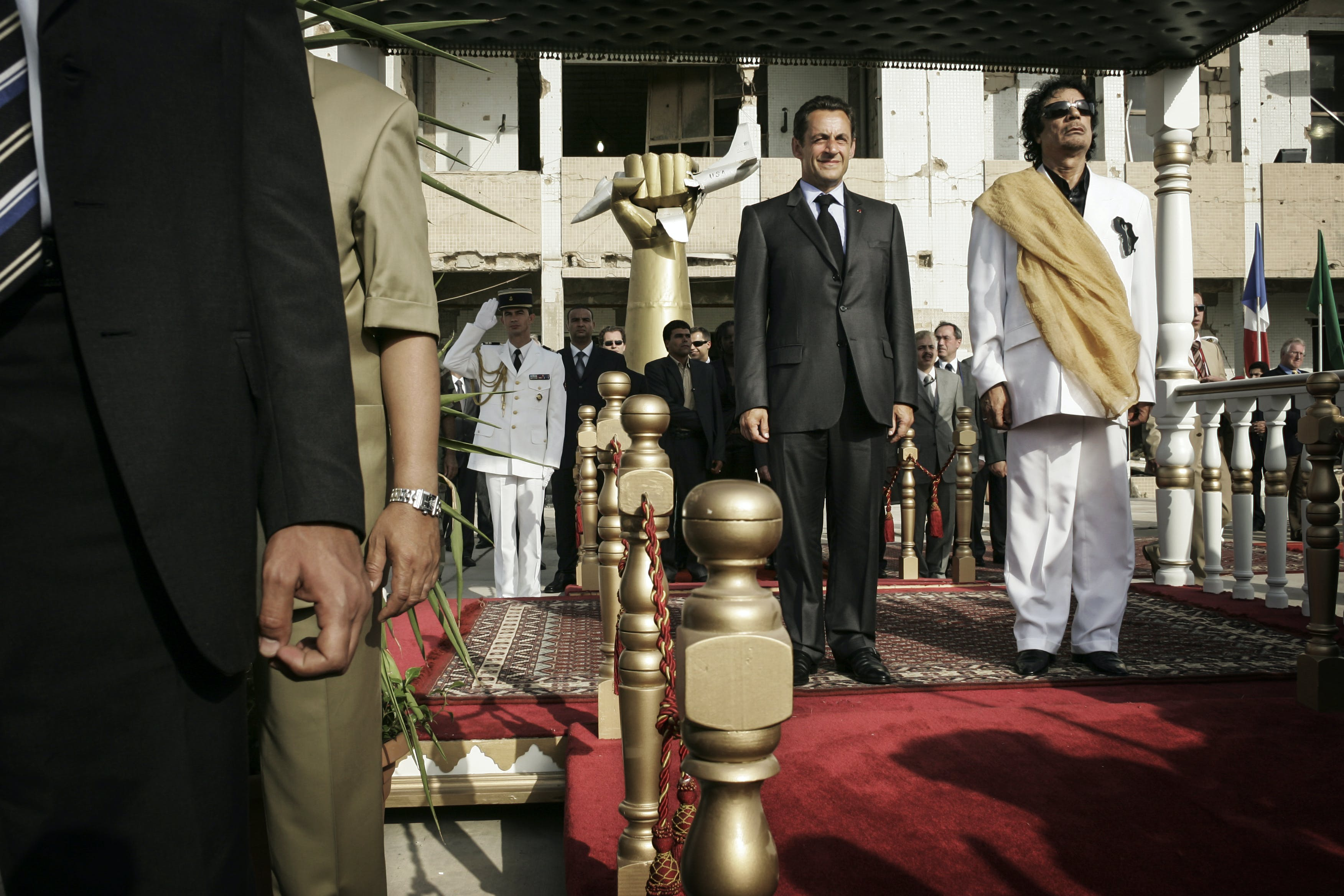 TRIPOLI,LIBYA - JULY 25: French President Nicolas Sarkozy is welcomed by Libyan Leader Muammar Gaddafi at Bab Al Azizya compound during an official visit in Tripoli, July 25th 2007. Both listening to national anthems.(Photo by Etienne de Malglaive/Getty Images)