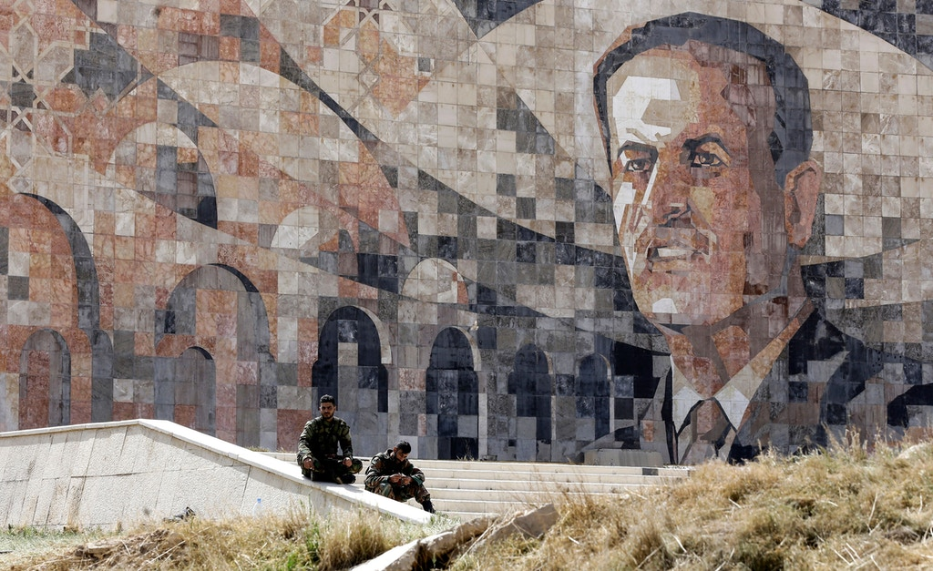 TOPSHOT - Syrian regime forces sit by a marble mosaic monument depicting a picture of late President Hafez al-Assad, at the entrance of Harasta in Eastern Ghouta on the outskirts of Damascus on March 25, 2018, after a deal was struck with rebels in the area to evacuate the town. / AFP PHOTO / LOUAI BESHARA        (Photo credit should read LOUAI BESHARA/AFP/Getty Images)