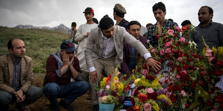 Friends and relatives of Agence France Presse (AFP) Afghanistan Chief Photographer Shah Marai Faizi gather at his burial in Gul Dara, Kabul on April 30, 2018, after his death in the second of two bombings that occurred in the Afghan capital. - Friends and colleagues of Shah Marai have reacted with shock and grief to news of the veteran AFP photographer's death in Kabul. Marai, who leaves behind six children, was one of at least nine journalists killed in twin suicide bomb attacks that rocked the Afghan capital. At least another 16 people were killed in the blasts. (Photo by Andrew Quilty / POOL / AFP) / RESTRICTED TO EDITORIAL USE        (Photo credit should read ANDREW QUILTY/AFP/Getty Images)