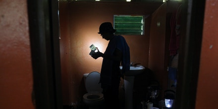 Ana Perez uses a solar lamp inside the bathroom of her home, after Hurricane Maria damaged the electrical grid in September 2017, in Naguabo, Puerto Rico January 26, 2018. REUTERS/Alvin Baez - RC1F8ED35970