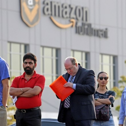 FILE - In this Wednesday, Aug. 2, 2017, file photo, applicants wait in line to enter a job fair at an Amazon fulfillment center, in Kent, Wash. Amazon has narrowed its search for a second headquarters city to 20 locations, concentrated mostly in the East and the Midwest. (AP Photo/Elaine Thompson, File)
