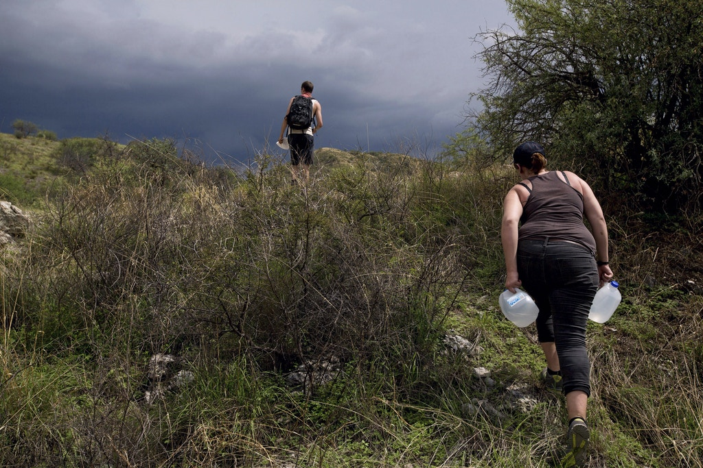 FILE -- William Berk and Lydia Delphia, volunteers with No More Deaths, hike through the desert, carrying water to drop for migrants near Arivaca, Ariz., July 25, 2013. The Border Patrol raided the humanitarian aid group's base camp in 2017, arresting four men who had crossed into the United States illegally and were at the camp receiving emergency medical care. (Josh Haner/The New York Times)