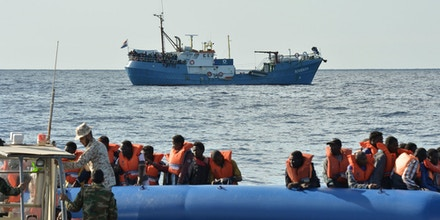 A picture taken on November 4, 2016 migrants and refugees sitting on a rubber boat as the Libyan coastguards patrol help them during a rescue operation with the