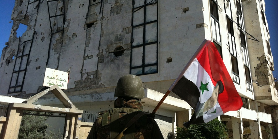 A Syrian army's soldier a national flag featuring Syria's President Bachar al-Assad in front of a building left in ruins with on June 5, 2013 in the city of Qusayr in Syria's central Homs province, after the Syrian government forces seized total control of the city and the surrounding region. The Syrian army ousted rebels from the strategic town of Qusayr after a blistering 17-day assault led by Hezbollah fighters, scoring a major battlefield success in a war that has killed at least 94,000 people.   AFP PHOTO / STR        (Photo credit should read -/AFP/Getty Images)