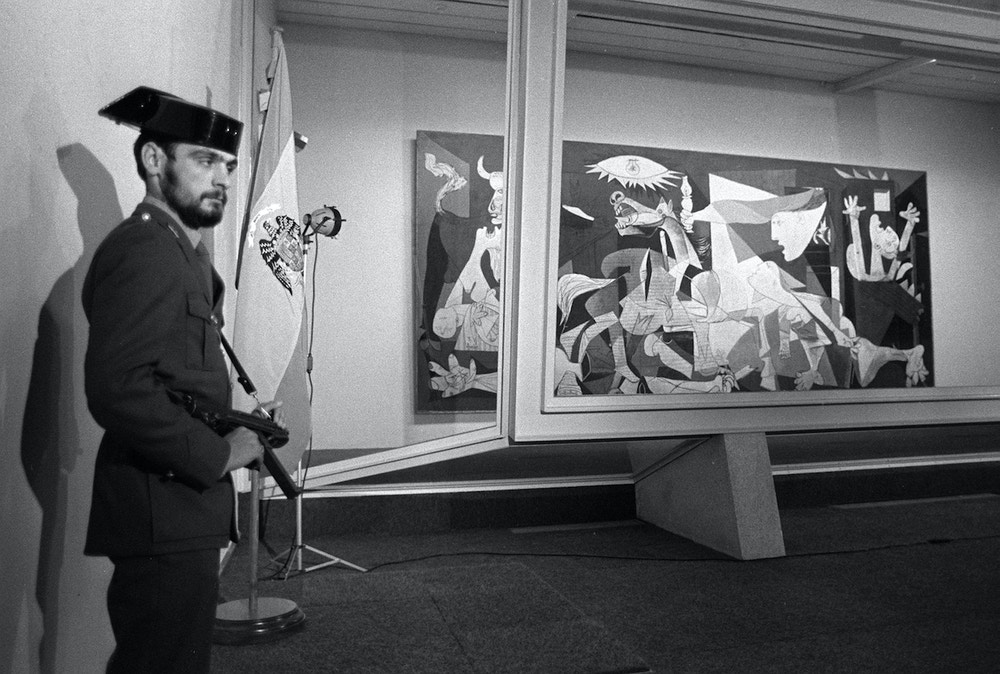 "A Spanish civil guard with an automatic weapon stands guard over Picasso's 1937 ""Guernica,"" a depiction of the Spanish Civil War, during a viewing by journalists and critics in Madrid, Spain on Oct. 23, 1981.  After years of negotiation and political disputes, the Picasso masterpiece had recently arrived on Spanish soil for the first time.  (AP Photo/Ive)"