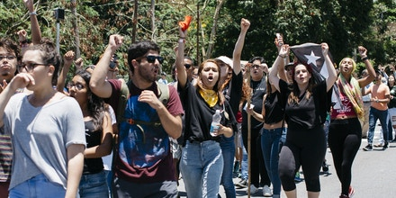 Students chant protests slogans during a picket line in front of the main entrance to the University of Puerto Rico, Rio Piedras Campus in San Juan, P.R., on Thursday, May 11, 2017. The university has been on strike for over a month to protest a proposed over $500 million cut in the institutionsÕ budget, and to demand the audit of the public debt. After a small group law students sued the dean and the administration of the campus to gain access to their classes, the court ordered the opening of the schoolÕs gates by 6:00AM today. Students, professors and citizens gathered from dawn at the U.P.R.Õs main gate in fears that the police would forcibly remove the students. Last week the governor of Puerto Rico announced the American territory would declare a type bankruptcy, as allowed under the Puerto Rico Oversight, Management, Economic Stability Act (PROMESA) to deal with its over $70 billion in public debt. (Photo by Erika P. Rodriguez)