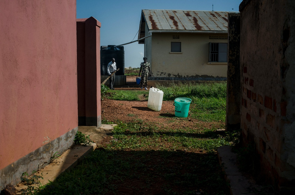 Villagers clean up the local health clinic prior to giving a family planning class  on March 26, 2018 in Parabongo, Uganda.