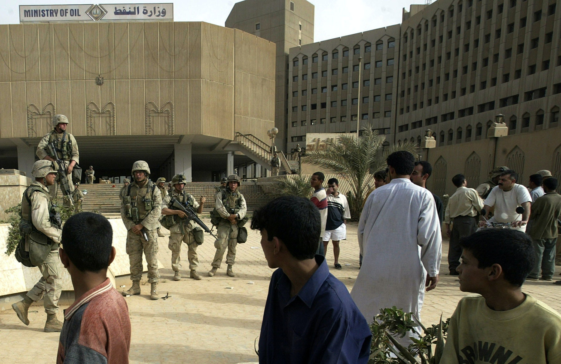 Iraqi children watch U.S. Marines after they took control of the Ministry of Oil building in Baghdad Wednesday, April 9, 2003. (AP Photo/Jerome Delay)