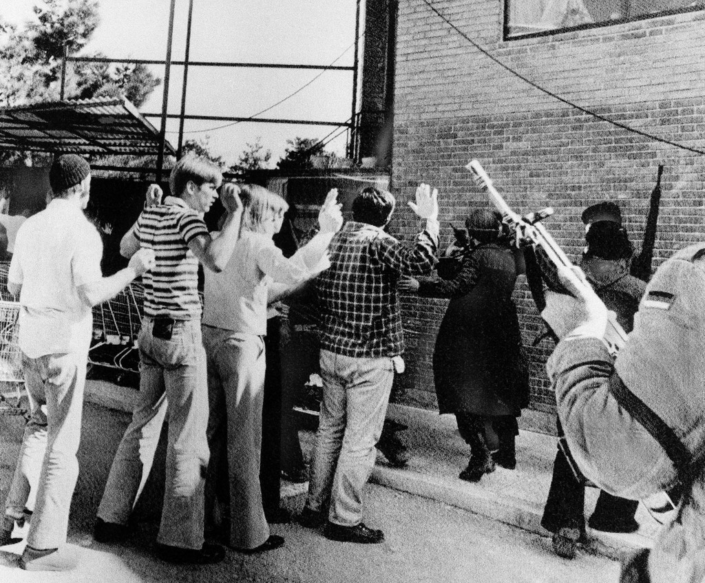Armed Iranian rebels search Americans who were living in the U.S. Embassy compound in Teheran, Feb., 14, 1979.  During the takeover of the embassy this group was taken from their living quarters, brought into the courtyard and searched. Later they were taken to another building while the attackers occupied the compound. (AP Photo)