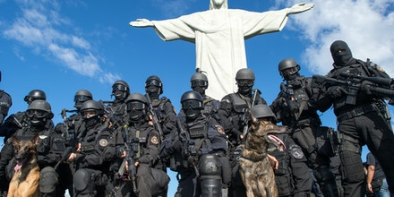 Members of the Elite Unit of the Brazilian Military Police (BOPE) pose under the Christ the Reedemer statue after practicing maneuvers on Corcovado Hill in Rio de Janeiro, Brazil, on April 6, 2013. Rio de Janeiro will host matches of the FIFA Confederation Cup in June and the 2013 World Youth Day international Catholic gathering in July.   AFP PHOTO / CHRISTOPHE SIMON        (Photo credit should read CHRISTOPHE SIMON/AFP/Getty Images)