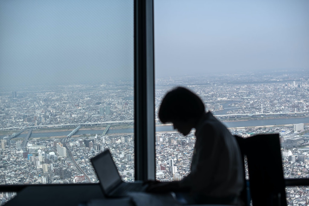 TOKYO, JAPAN - MARCH 29:  A cafe employee works on her laptop on the viewing platform of the Tokyo Skytree on March 29, 2018 in Tokyo, Japan. The tower was opened to the public in May 2012 and is the tallest tower in the world and the second tallest structure in the world after the Burj Khalifa in Dubai. It is primarily a television and radio broadcast site for Japan's Kanto region but is also a popular tourist site attracting thousands of visitors each month.  (Photo by Carl Court/Getty Images)