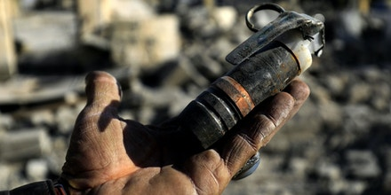 A picture taken on January 16, 2018 shows a Syrian man holding an undetonated mine that was left by the Islamic State (IS) group in Raqa.The Islamic State group was ousted from its de facto Syrian capital Raqa in October, but it left an ocean of mines scattered across the ravaged city. / AFP PHOTO / Delil souleiman (Photo credit should read DELIL SOULEIMAN/AFP/Getty Images)