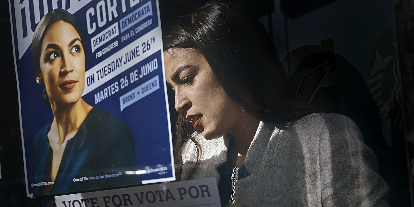 Congressional candidate Alexandria Ocasio-Cortez, left, paste posters in Bronx, New York, Saturday, April 21, 2018. (Photo: Andres Kudacki)