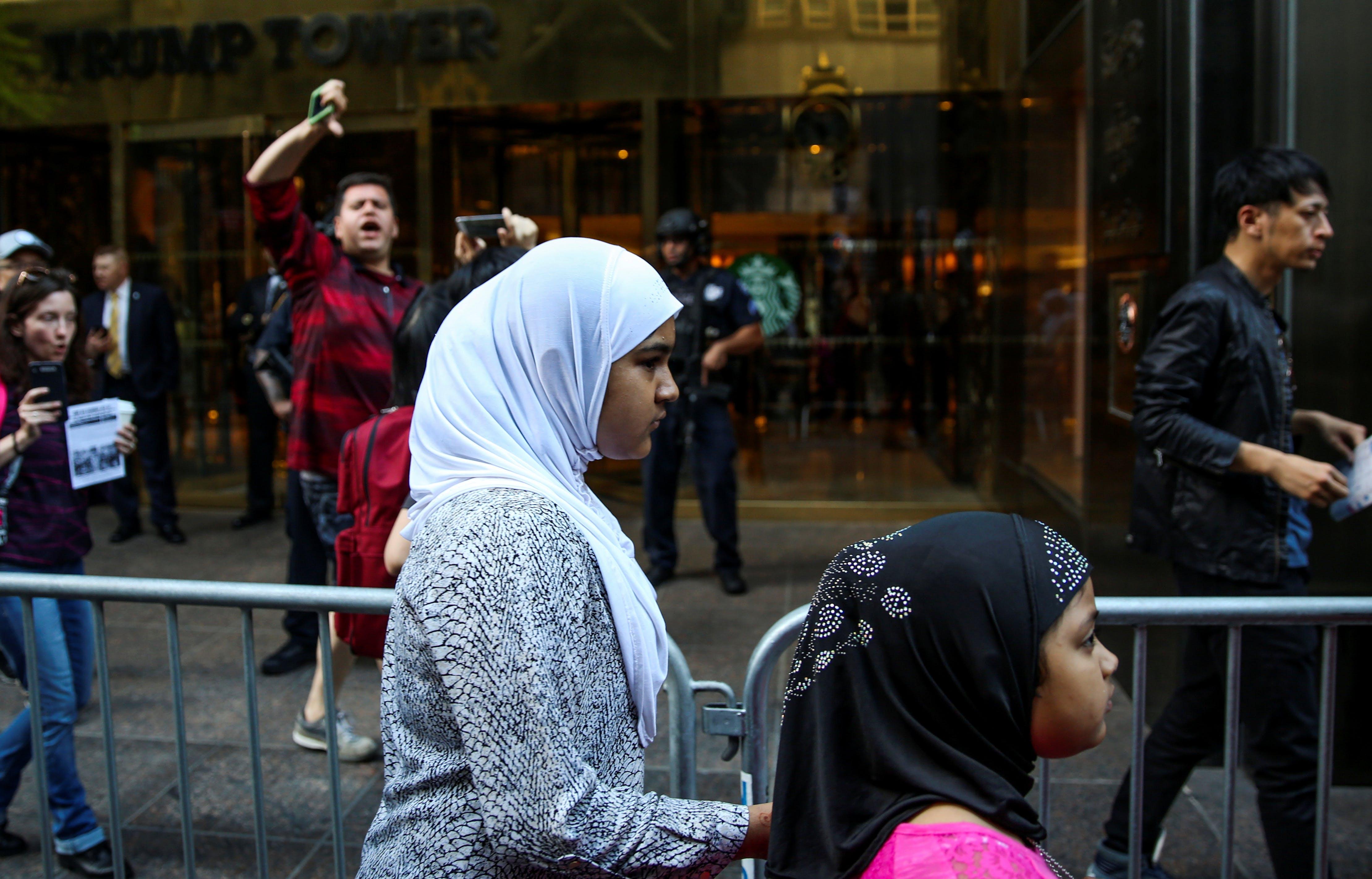 Garotas muçulmanas em hijabs passam por um homem, enquanto ele grita e desiste de ativistas (não retratados) protestando do lado de fora da Trump Tower contra a decisão da Suprema Corte dos EUA de reviver partes de uma proibição de viagem de pessoas de seis países de maioria muçulmana em Manhattan, Nova York, EUA, 26 de junho de 2017. REUTERS / Amr Alfiky - RC1DBA1B62A0