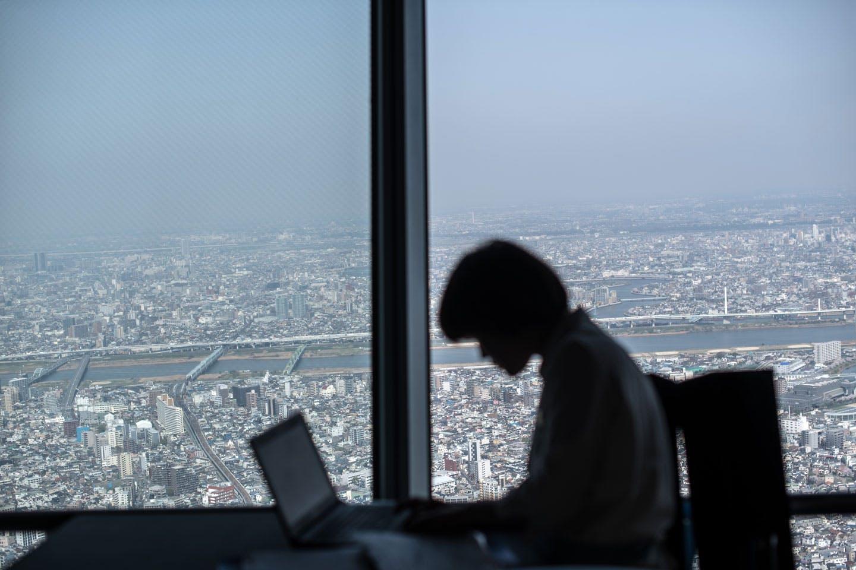 Uma mulher trabalha com seu laptop no andar panorâmico da torre Tokyo Skytree, no dia 29 de março de 2018, em Tóquio, no Japão.