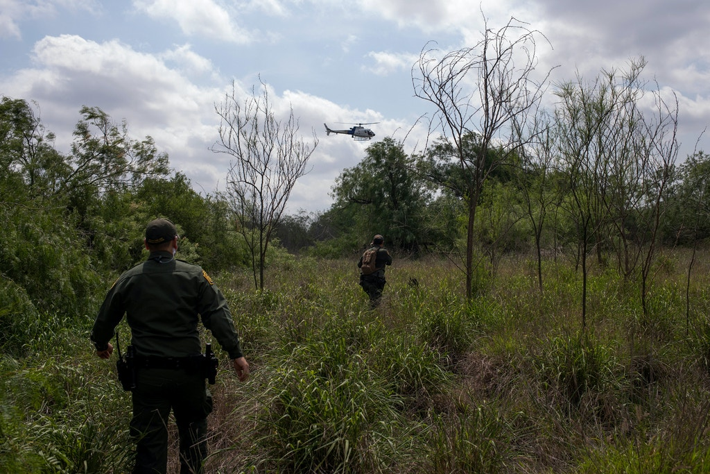 Border patrol agents in a helicopter and with a canine unit search for illegal immigrants along the border with Mexico near McAllen, Texas, U.S., May 2, 2018.  REUTERS/Adrees Latif - RC1BCF061090