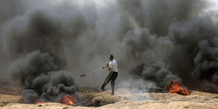 Palestinian protesters take part during clashes after protests near the border with Israel on May 14, 2018.