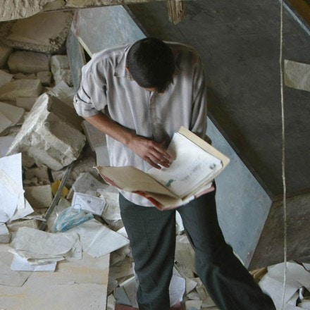 An Iraqi civilian looks through personal files, Thursday April 10, 2003, scattered on the floor of the bombed out White Lion, the building that housed the secret police documents, jail cells, and interrogation chambers where Saddam Hussein's Baath Party  leaders kept political prisoners in basra, Iraq. (AP Photo/David Guttenfelder)