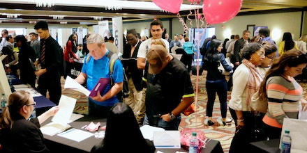 FILE- In this Jan. 30, 2018, file photo, job applicants talk with employees of Hialeah Park, at a JobNewsUSA job fair in Miami Lakes, Fla. On Friday, May 4, the U.S. government issues the April jobs report. (AP Photo/Lynne Sladky, File)