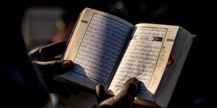 A man from Sudan reads the Koran at the migrant camp known as the