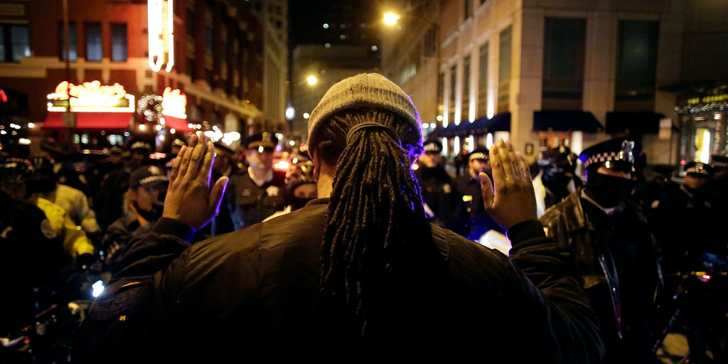 CHICAGO, IL - NOVEMBER 27 : A man stands with his hands up as he  protest the shooting of Laquan McDonald who was killed by a Chicago police officer November 27, 2015 in Chicago, Illinois. Chicago police officer Jason Van Dyke was charged Tuesday with first degree murder for fatally shooting 17-year-old McDonald 16 times last year on the southwest side of Chicago after Van Dyke was responding to a call of a knife wielding man. The dash-cam video of officer Van Dyke shooting McDonald was released by the Chicago Police department earlier this week after a judge denied Van Dyke bail during his bond hearing at Leighton Criminal Court. (Photo by Joshua Lott/Getty Images)