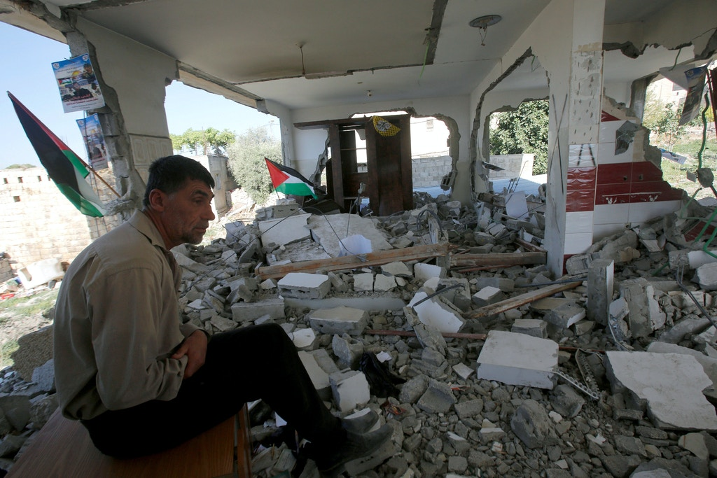 Mohamad, the father of Palestinian assailant Bashar Masalha, looks at damage of their house after it was partially demolished by the Israeli forces, in the West Bank village of Hajja near Qalqilya June 21, 2016. REUTERS/Abed Omar Qusini   - S1AETLDNOAAA