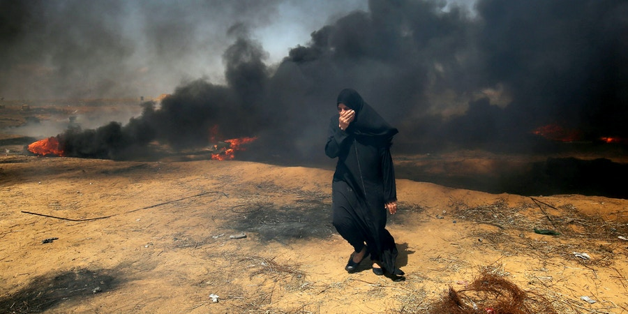 A Palestinian woman covers her face as smoke billows around her during clashes with Israeli forces along the border with the Gaza strip east of Khan Yunis on May 11, 2018, as Palestinians demonstrate for the right to return to their historic homelands in what is now Israel. - Over fifty Palestinians have been killed by Israeli fire since protests and clashes began on March 30 calling for Palestinian refugees to be able to return to their former homes in what is now Israel. (Photo by SAID KHATIB / AFP)        (Photo credit should read SAID KHATIB/AFP/Getty Images)